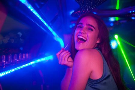Mujer joven que se ríe de la barra en el club nocturno LANG_EVOIMAGES