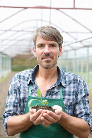 checker: Portrait of organic farmer holding seedling in polytunnel LANG_EVOIMAGES