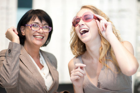 Two women laughing whilst trying on eyeglasses LANG_EVOIMAGES