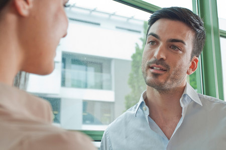 low self esteem: Two young colleagues having flirtatious meeting in office