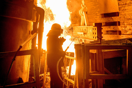 Steel worker in front of furnace fire in steel foundry LANG_EVOIMAGES