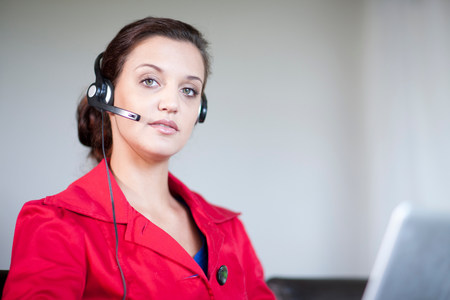 Young woman wearing telephone headset LANG_EVOIMAGES