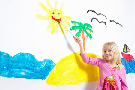 well behaved: Young girl painting smiling sunshine face on wall