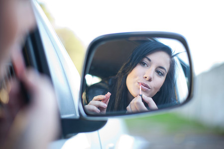 Young woman applying lipstick in car mirror LANG_EVOIMAGES