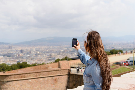 information superhighway: Young female tourist photographing view of Barcelona city,Spain LANG_EVOIMAGES