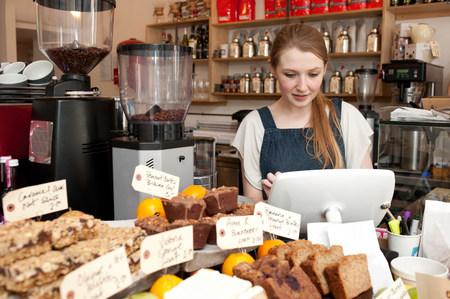 cash register building: Young woman using cash register in cafe
