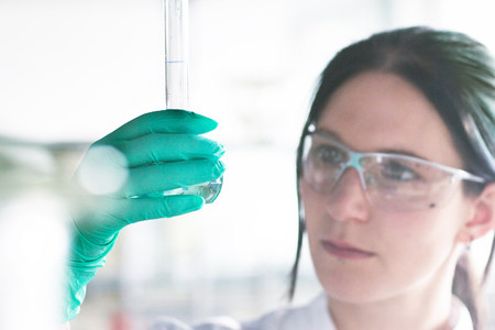 gloved: Close up of female scientist examining at test tube