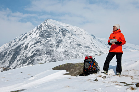 winter escape: Female climber with map on snow covered mountain,Carneddau,Snowdonia