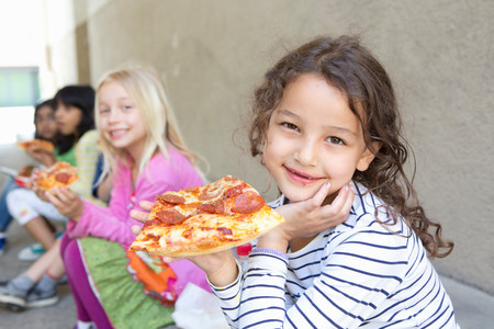 Group of children eating pizza outdoors LANG_EVOIMAGES