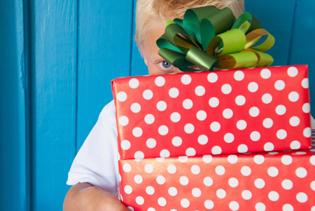 Boy peeping behind gifts in hand LANG_EVOIMAGES