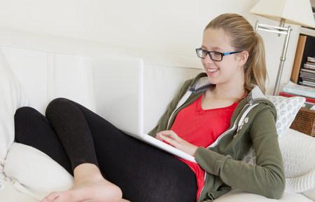 receding: Teenage girl using laptop on sofa,smiling