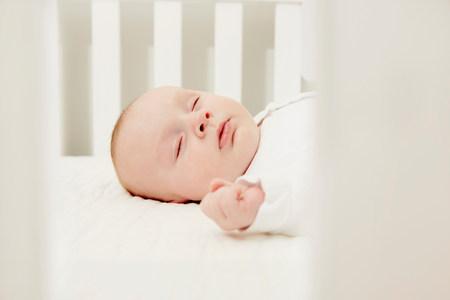 puños cerrados: Bebé en el dormir de la cuna