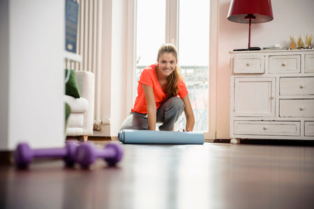 go inside: Young woman rolling up exercise mat at home