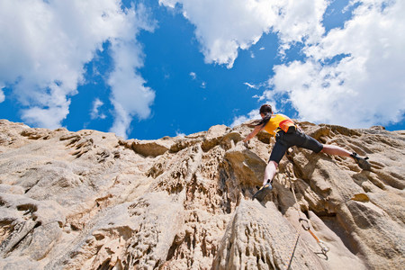 Female rock climber nearing cliff top