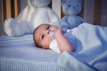 babys dummies: Baby boy and teddy bears in crib at night