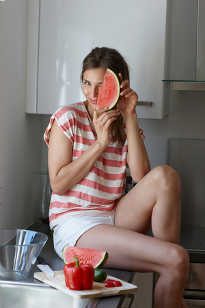 impulsive: Woman covering face with slice of watermelon