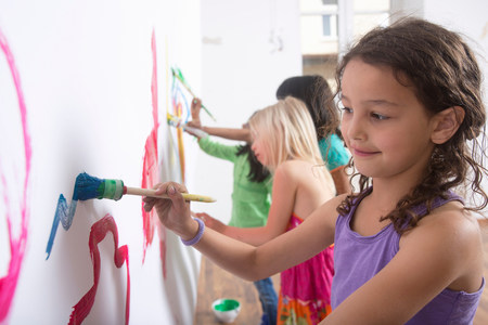 well behaved: Group of girls painting wall LANG_EVOIMAGES
