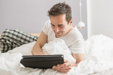 palm reading: Mid adult man lying on bed using digital tablet LANG_EVOIMAGES