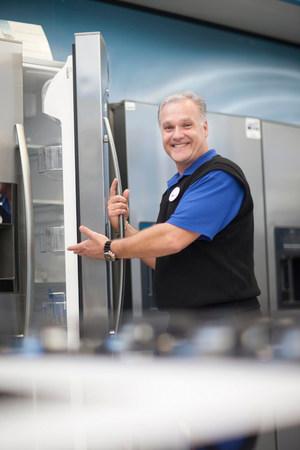 clothing store: Salesman showing fridge in showroom LANG_EVOIMAGES