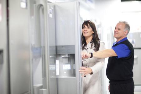 Woman looking at refrigerators in showroom LANG_EVOIMAGES