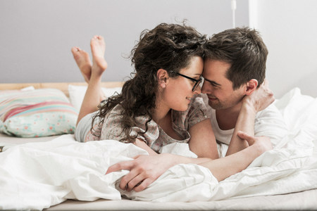 chillout: Mid adult couple wearing pyjamas lying on front on bed,face to face