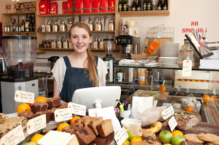 cash register building: Young woman behind kitchen counter in cafe LANG_EVOIMAGES