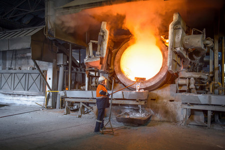 gloved: Worker raking liquid aluminum from furnace at recycling plant
