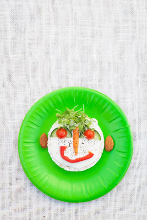 Face made from fresh food on green plate LANG_EVOIMAGES