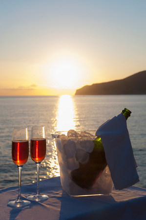 refreshed: Wine glasses and bottle in ice bucket with sea in background LANG_EVOIMAGES
