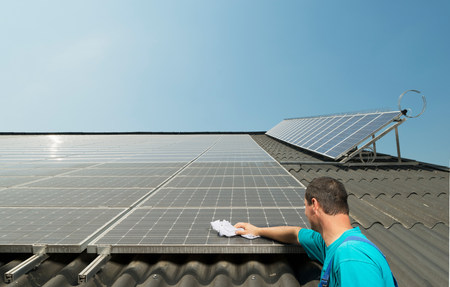 german ethnicity: Farmer cleaning solar panels on barn roof,Waldfeucht-Bocket,Germany LANG_EVOIMAGES