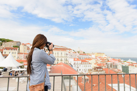 sight seeing: Young female tourist photographing in Alfama District,Lisbon,Portugal LANG_EVOIMAGES