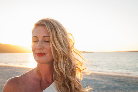 shutting: Blond woman with eyes closed on beach at dusk,Cape Town,South Africa