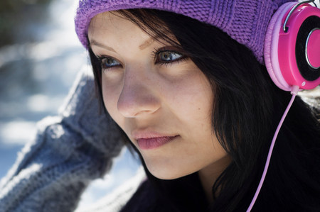 Close up portrait of young female listening to headphones