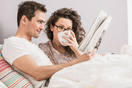 Mid adult couple reading newspaper in bed,drinking coffee