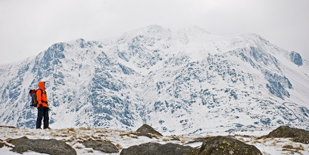 winter escape: Female climber in front of snow covered mountain,Y Garn,Snowdonia LANG_EVOIMAGES