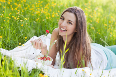 Young woman in field of buttercups eating strawberries LANG_EVOIMAGES