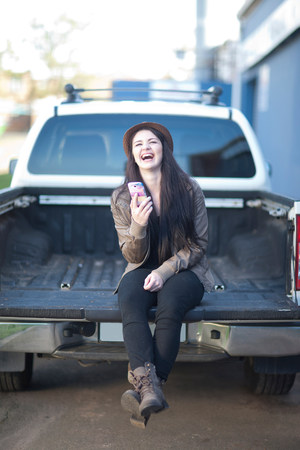 jesting: Portrait of young female sitting on back of truck