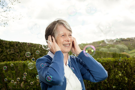 60 64 years: Senior woman covering ears and laughing at bubbles LANG_EVOIMAGES