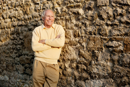 living idyll: Senior man leaning against stone wall with arms crossed LANG_EVOIMAGES