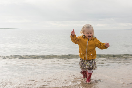 Toddler paddling at coast