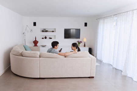 Husband and wife relaxing on corner sofa in living room LANG_EVOIMAGES