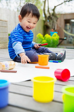 only 3 people: Male toddler drawing in garden LANG_EVOIMAGES