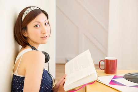 sleeveless top: Woman looking up from book LANG_EVOIMAGES