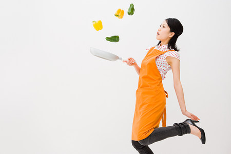 Woman tossing peppers LANG_EVOIMAGES