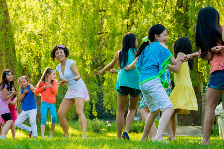 preadolescent: Woman and group of girls doing tug of war in park LANG_EVOIMAGES