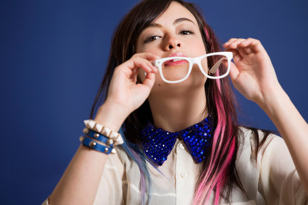 Portrait of young woman with dyed hair holding glasses LANG_EVOIMAGES