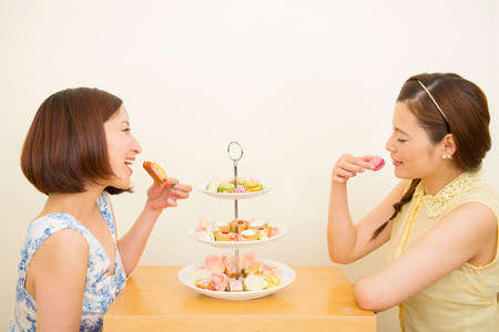 Two happy women enjoying dessert from three tiered cake stand LANG_EVOIMAGES