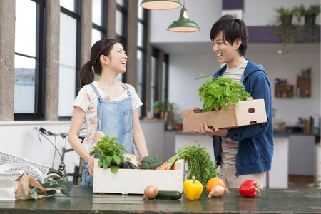 cardboard only: Portrait of young couple in kitchen with herbs and vegetables