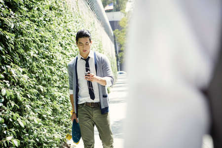 earbud: Young man walking down street carrying skateboard and smartphone LANG_EVOIMAGES