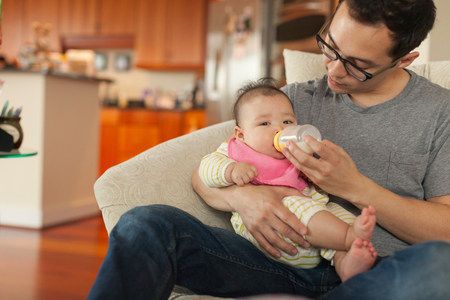 front house: Father sitting on sofa feeding baby daughter